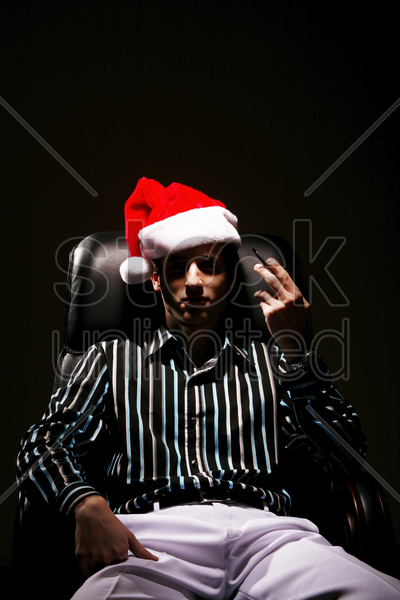 businessman with christmas hat smoking cigarette stock photo
