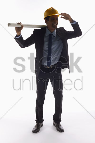 businessman with construction helmet holding a roll of paper stock photo
