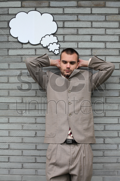 businessman with eyes closed and a thought bubble above his head stock photo