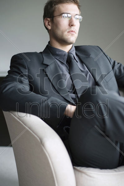 businessman with glasses sitting on the couch thinking stock photo