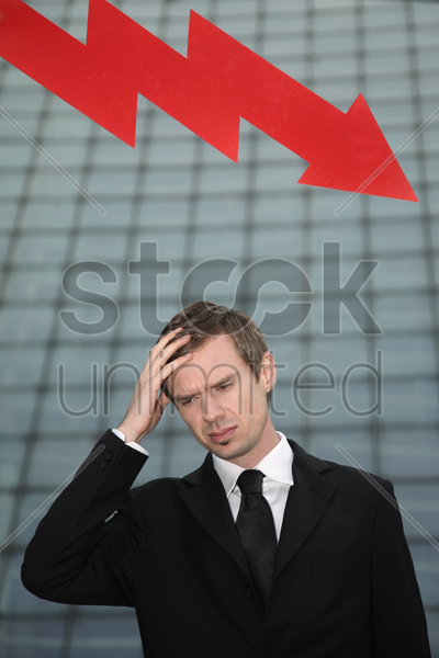 businessman with hand on forehead and arrow pointing down in the background stock photo