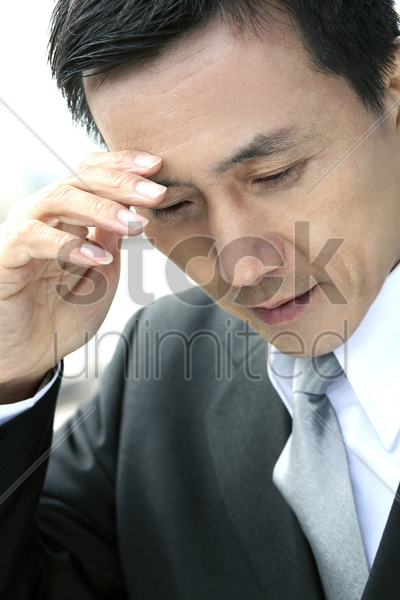businessman with hand on head stock photo