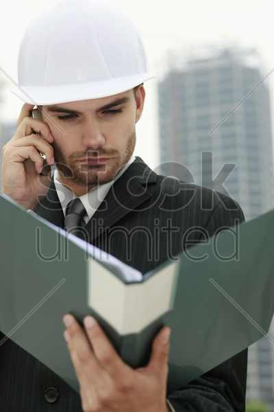 businessman with hard hat talking on the phone and reading document in file stock photo