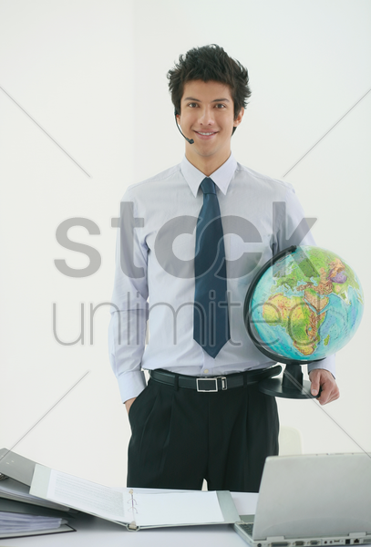 businessman with headset holding a globe stock photo