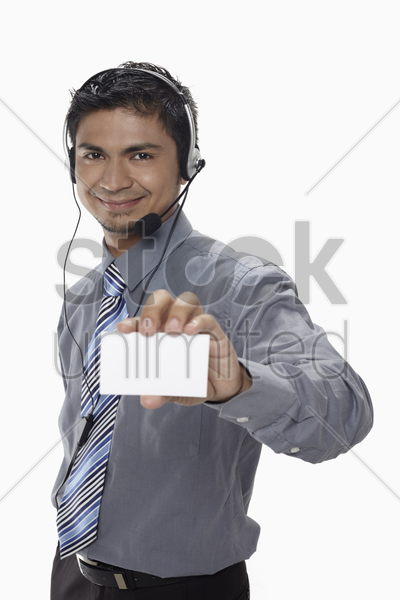 businessman with headset showing business card stock photo