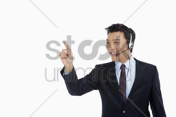 businessman with headset showing hand gesture stock photo