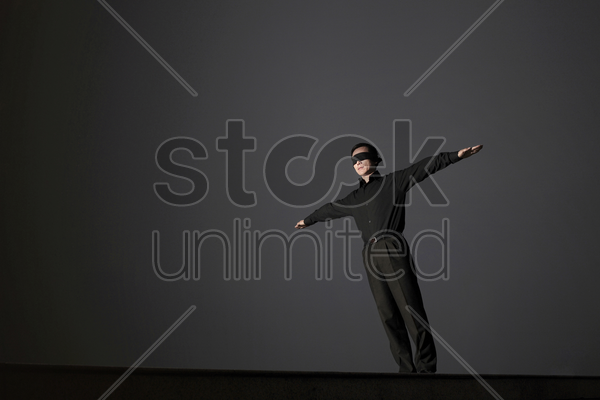 businessman with his eyes being blindfolded spreading his hands stock photo