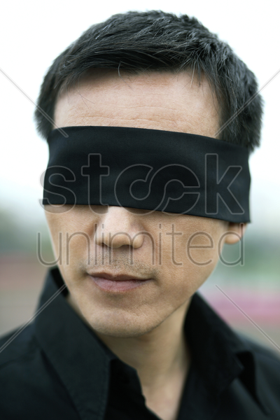 businessman with his eyes being blindfolded stock photo