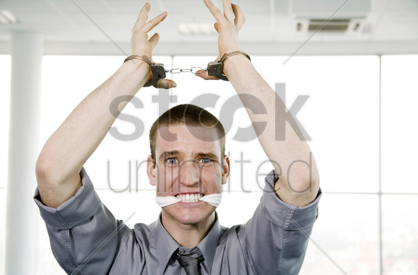 businessman with his hands being cuffed and his mouth being stuffed with cloth stock photo