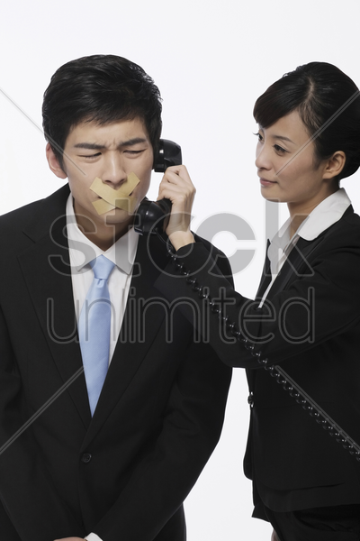 businessman with his mouth taped, businesswoman holding telephone receiver near his ear stock photo