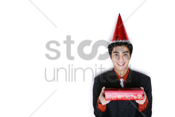 businessman with party hat holding a gift stock photo