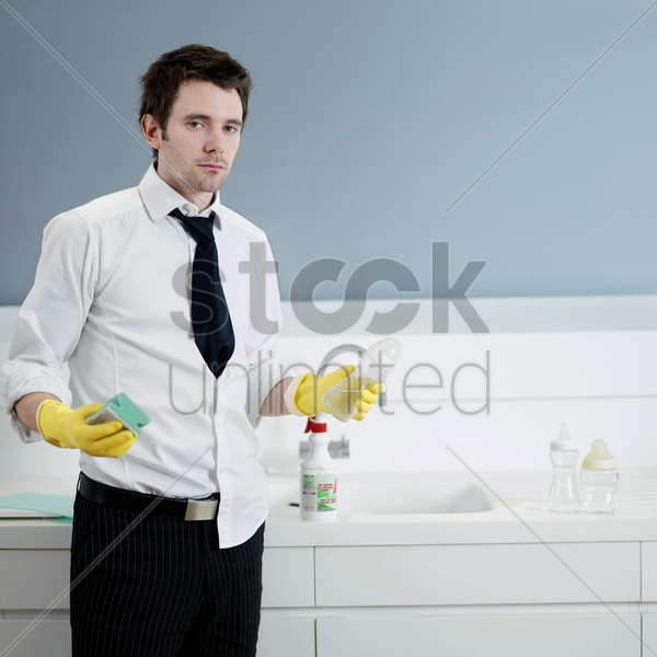 businessman with rubber gloves holding milk bottle and sponge stock photo