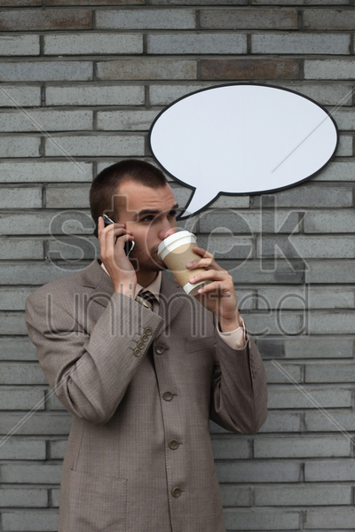 businessman with speech bubble talking on the phone and drinking coffee stock photo