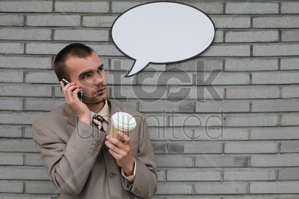 businessman with speech bubble talking on the phone and holding a cup of coffee stock photo