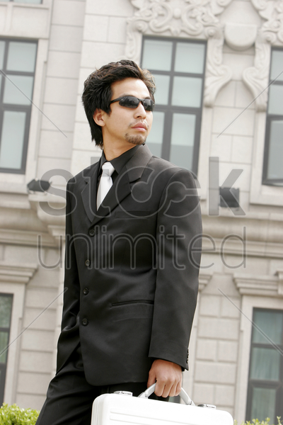 businessman with sunglass carrying a briefcase stock photo