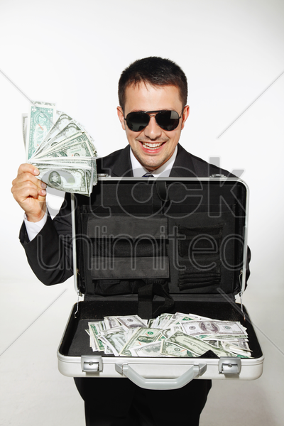 businessman with sunglasses showing a briefcase of money stock photo