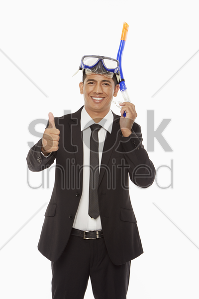 businessman with swimming gear giving thumbs up stock photo