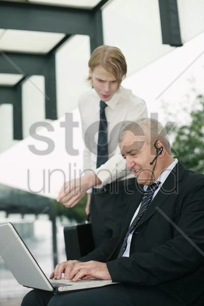 businessman with telephone headset using laptop, another businessman pointing at the screen stock photo