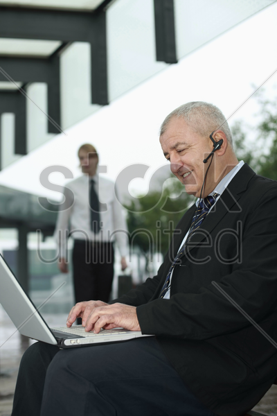 businessman with telephone headset using laptop stock photo