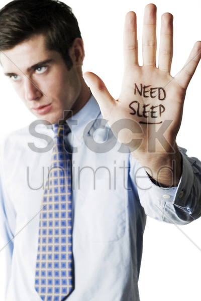 businessman with the word 'need sleep' written on his palm stock photo
