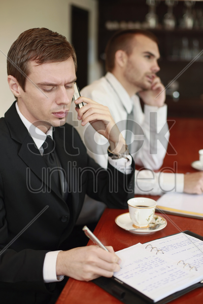 businessman writing on organizer while talking on the phone stock photo