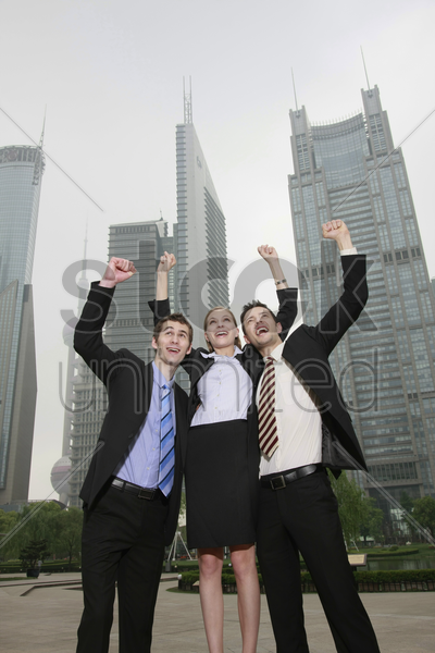 businessmen cheering with arms raised stock photo