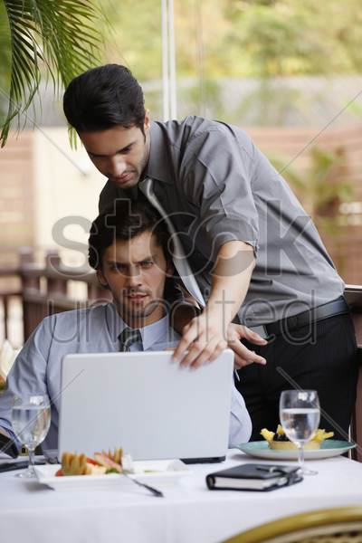 businessmen discussing work over lunch at restaurant stock photo