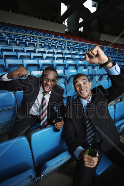businessmen drinking and cheering in stadium stock photo