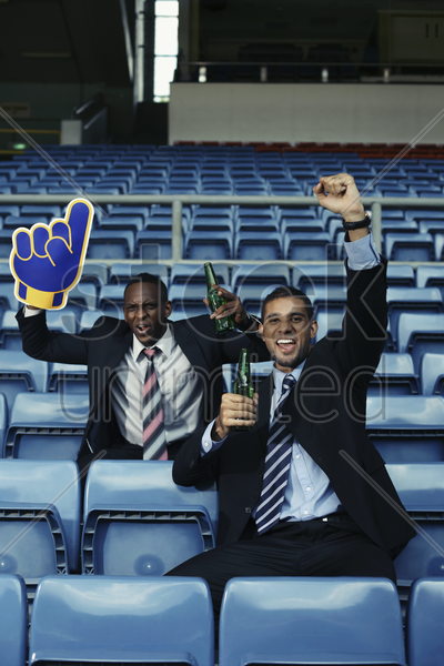 businessmen drinking beer and cheering in stadium stock photo