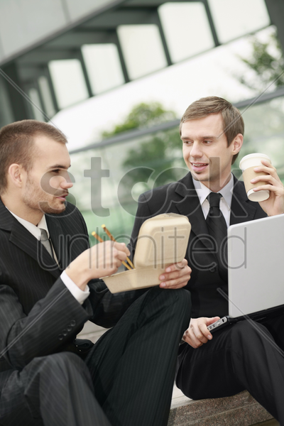 businessmen eating while working outdoors stock photo