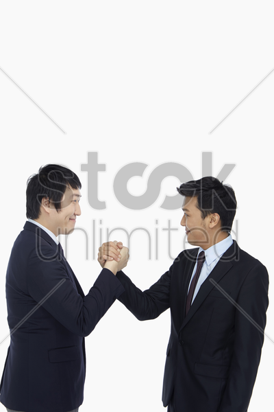 businessmen giving each other a handshake stock photo
