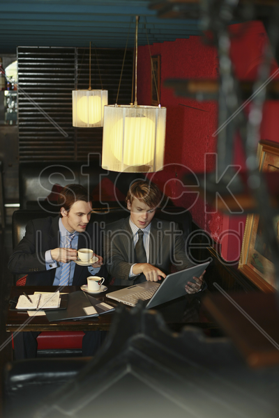 businessmen having discussion and using laptop stock photo