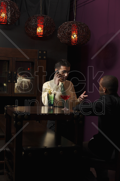businessmen having discussion over glasses of cocktails stock photo