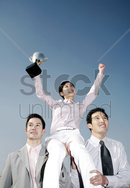 businessmen lifting up a female winner stock photo