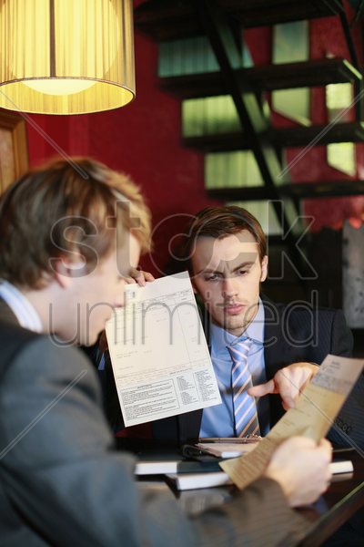 businessmen looking at documents stock photo