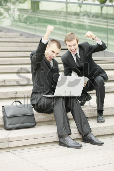 businessmen looking at laptop and raising fist stock photo