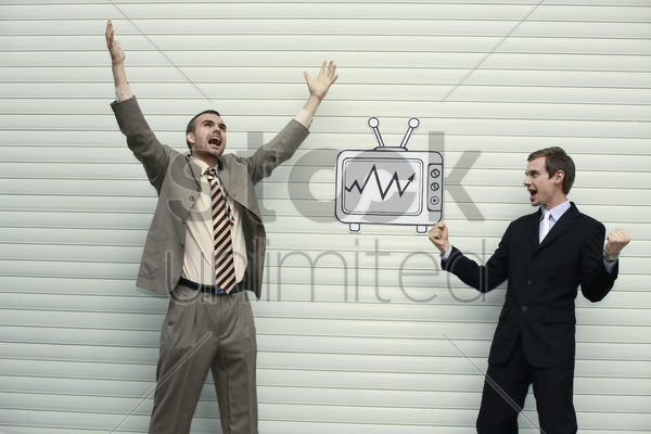 businessmen looking at television for stock market updates stock photo