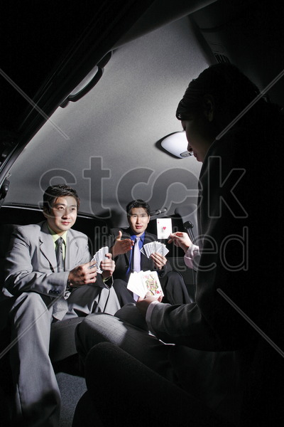 businessmen playing cards in the car stock photo