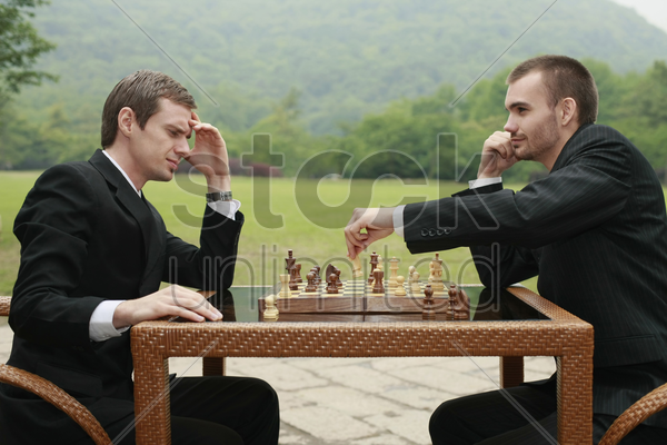 businessmen playing chess outdoors stock photo