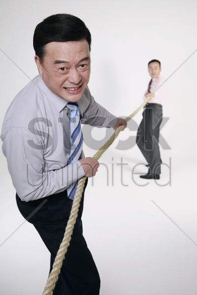 businessmen playing tug of war stock photo