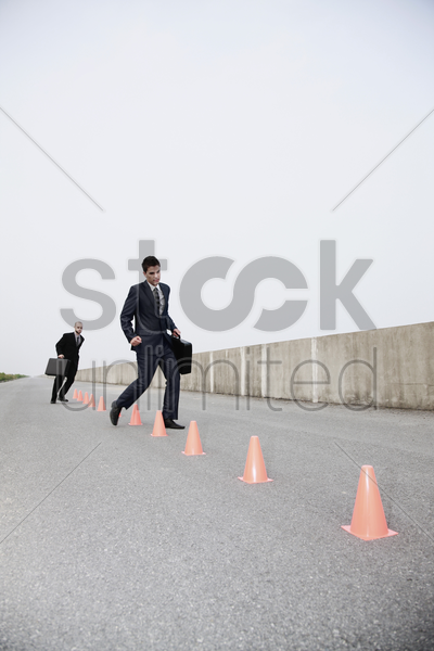businessmen running in between traffic cones stock photo