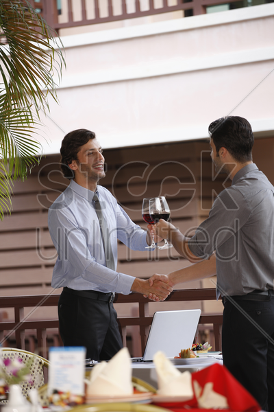 businessmen shaking hands and toasting red wine stock photo