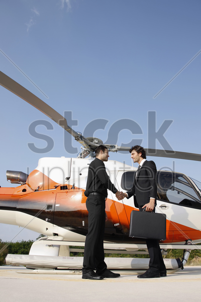 businessmen shaking hands by helicopter stock photo