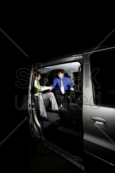 businessmen shaking hands in the car stock photo