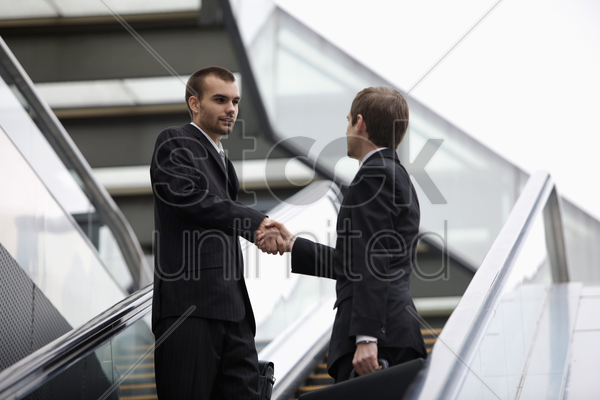 businessmen shaking hands on escalator stock photo