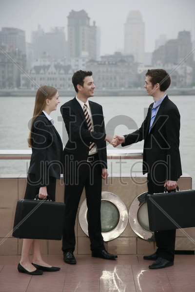 businessmen shaking hands with businesswoman watching at the side stock photo