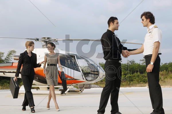 businessmen shaking hands with pilot while businesswomen are walking away from helicopter stock photo