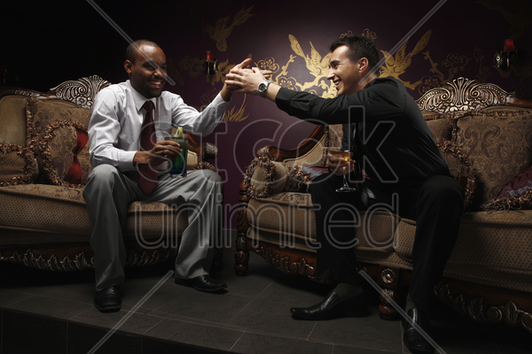 businessmen sitting on antique sofa talking while having cocktails stock photo