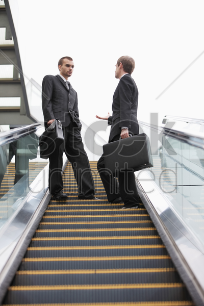 businessmen talking on escalator stock photo