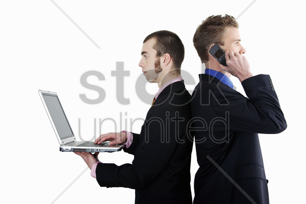 businessmen talking on the cell phone and using laptop stock photo